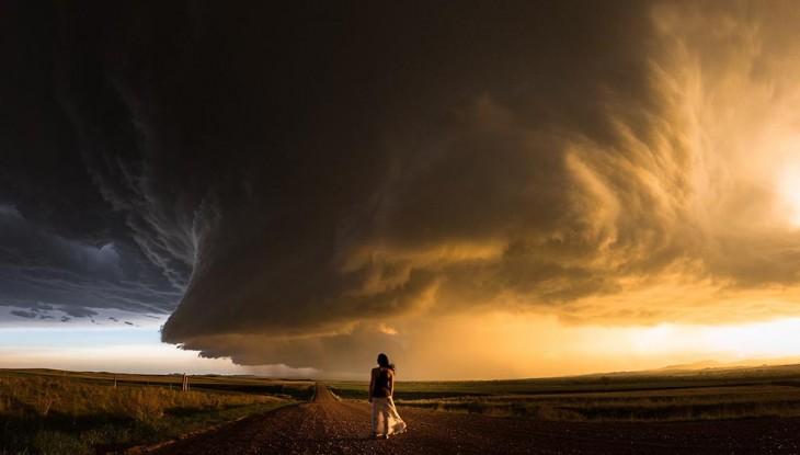 mujer parada a la mitad de un camino de tierra que divide dos terrenos y una forma de viento en el cielo