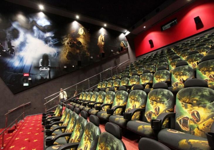 Sala de un cine con un estilo moderno y en sus asientos diseños de cobras y personajes de películas de acción