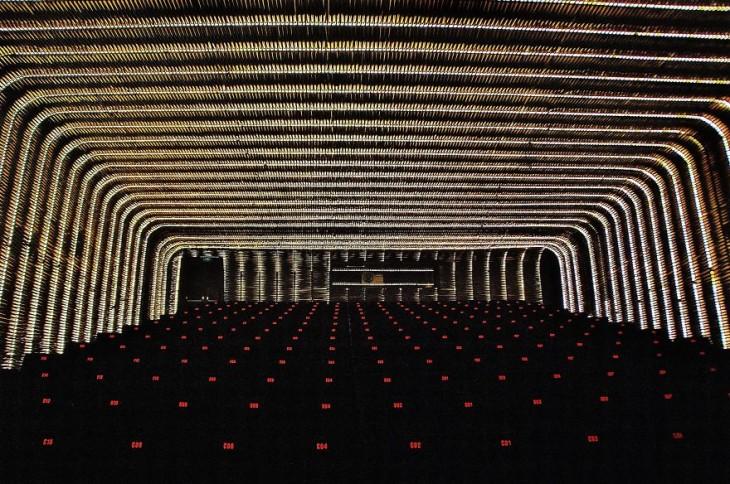 Vista frontal obscura de un cine en madrid españa con luces en los asientos y arcos con luces en el techo
