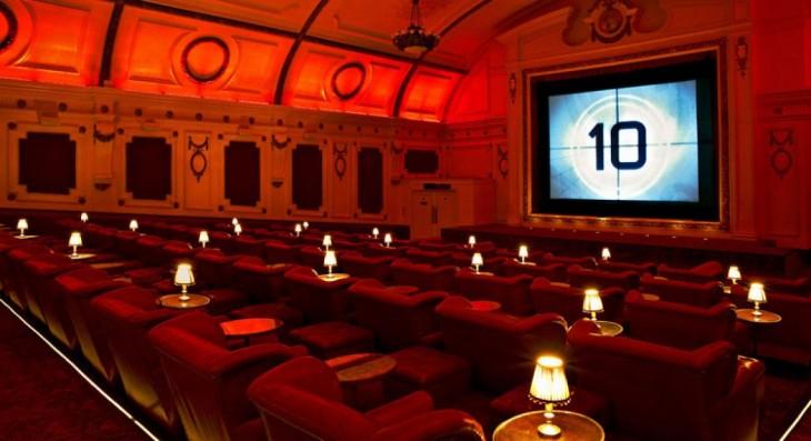 cine ubicado en Notting Hill con lámparas a un costado y sillones muy cómodos
