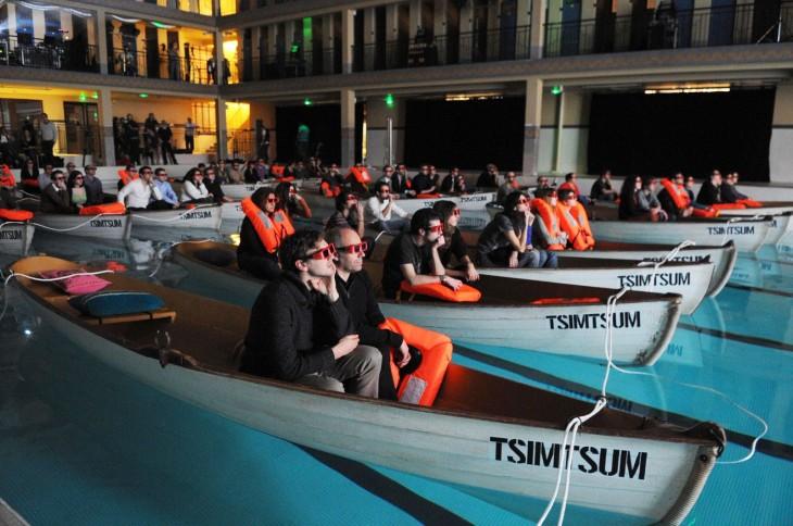 Personas en botes de remo con lentes en tercera dimensión en un cine de París