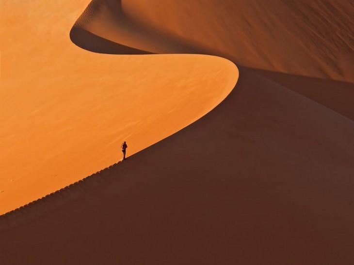 """Hombre caminando por la cima de un desierto conocido como """"Namib"""""""