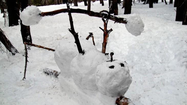 Muñeco de nieve colgando de una rama