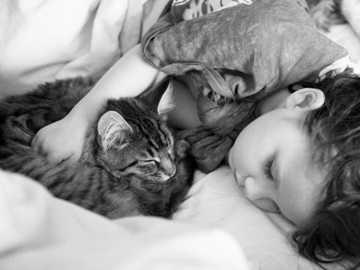 Imagen en blanco y negro de una niña abrazada de su gato mientras duerme