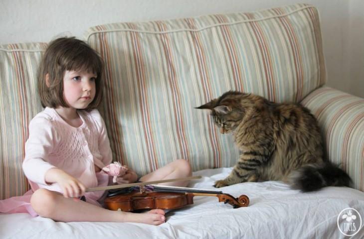 Niña con un violín y su gato en un sillón