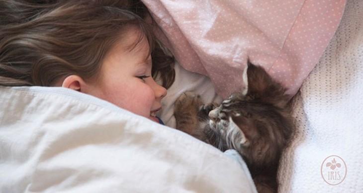 Niña sonriendo junto a su gato en una cama tapada hasta la cabeza