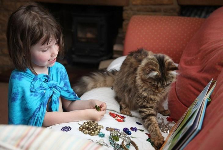 Niña y su gato sobre un sillón con algunos aretes y pulseras en la mano