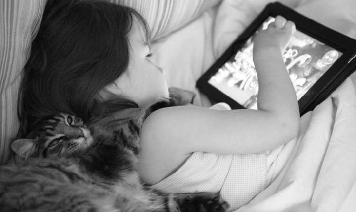 Niña usando un iPad y su gato trás de ella