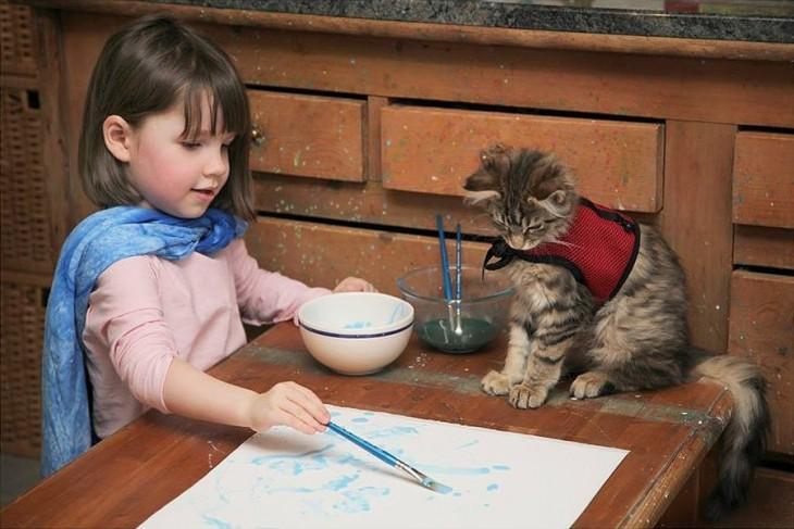 Niña frente a una mesa con un pincel en la mano pintando sobre una hoja y un gato a su lado