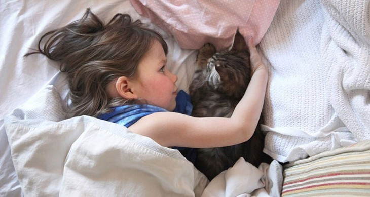 Niña recostada en la cama abrazando a su gato
