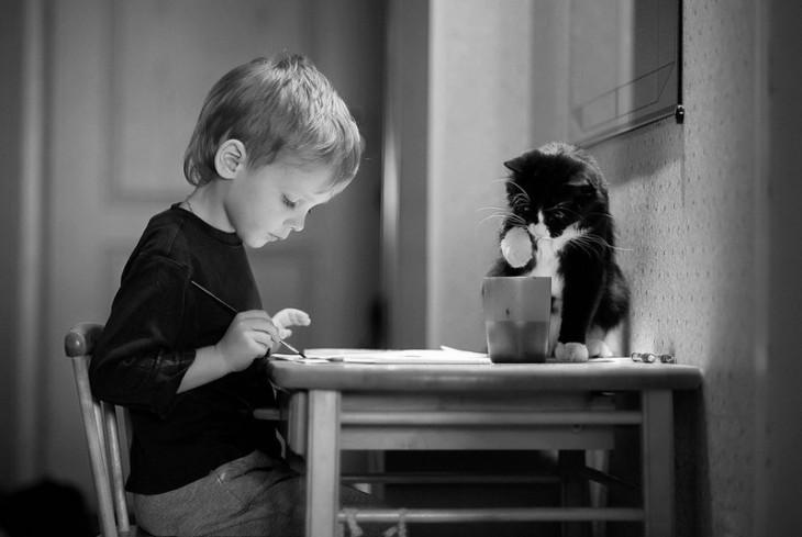 Niño pintando con un gato frente a él en una mesa