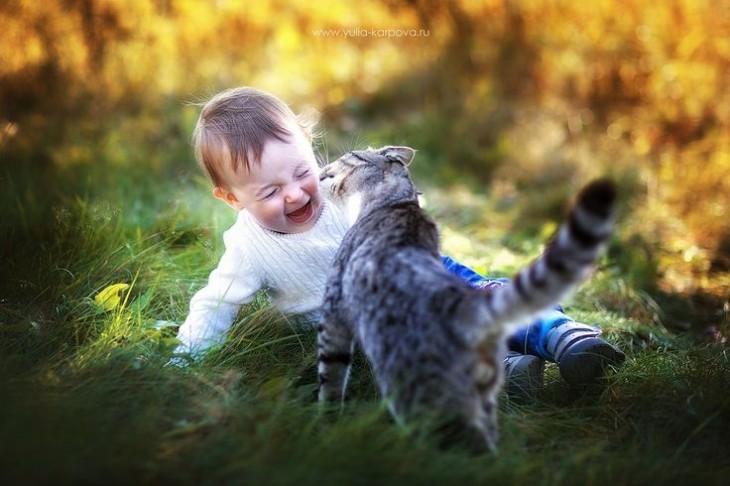 Niño riendo al jugar con su gato sobre un pasto