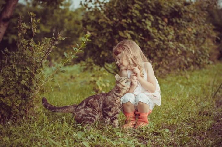 Una niña y su gato en un jardín