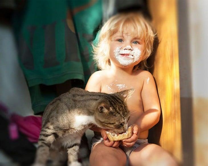 Niño sentado dando de comer a su gato