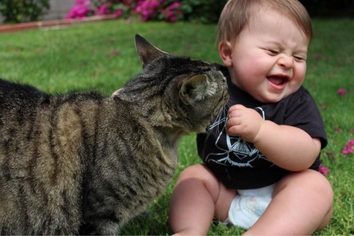 Niño junto a su gato en un jardín