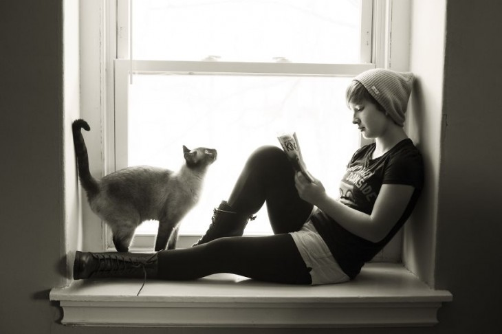 Chica acostada en una ventana y un gato frente a ella