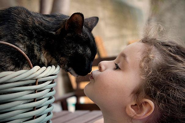 Niña dando un beso a su gato