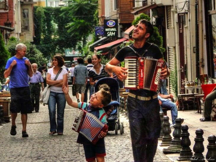 Un padre a un lado de su hijo con un acordeón cada uno