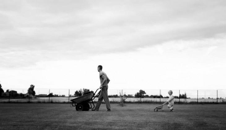 un niño atrás de su papa con una carretilla cada uno