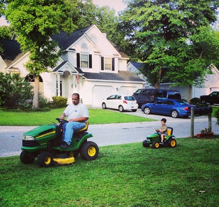 Padre e hijo en un jardín con podadoras