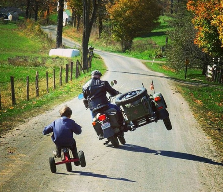 Padre e hijo haciendo la misma pose con su triciclo y motocicleta