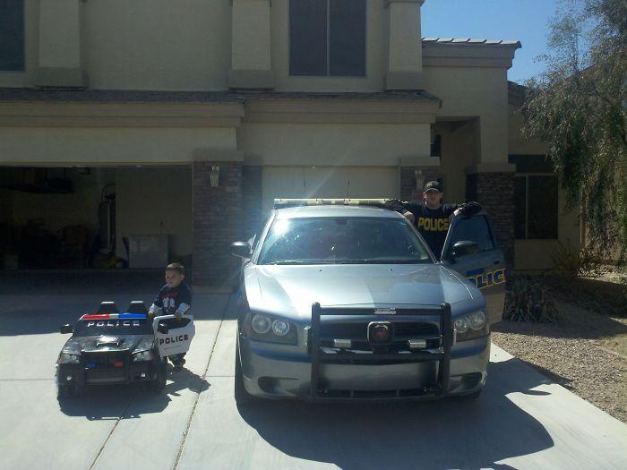 Padre e hijo subiéndose a un carro de policia