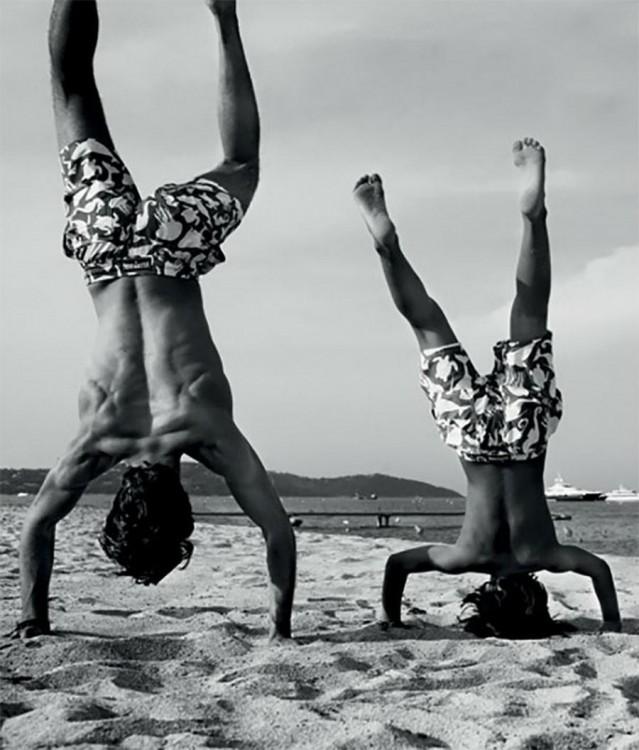 Padre e hijo parados de manos en una playa