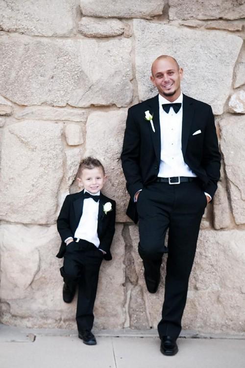 Padre e hijo con traje de vestir recargados en una pared