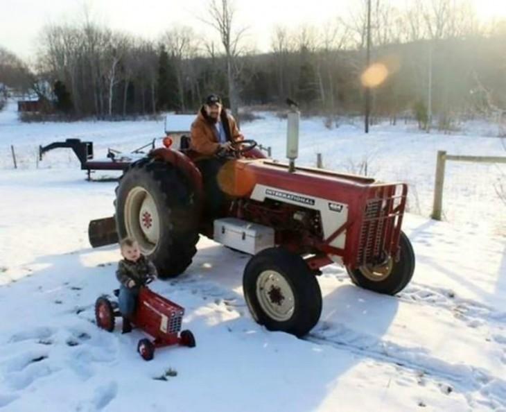 Un padre con su hijo cada uno en un tractor en la nieve