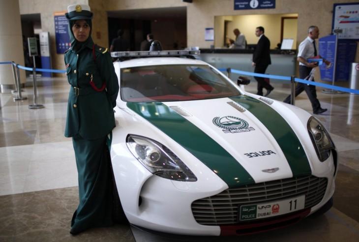 Agente mujer de la policía de Dubai a un costado de una de las lujosas patrullas