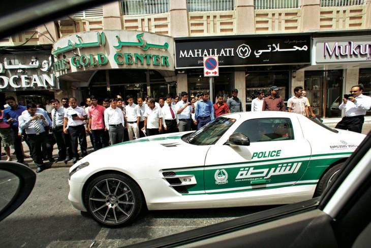 Patrulla pasando por la calle y personas a la orilla de una calle observando los carros deportivos