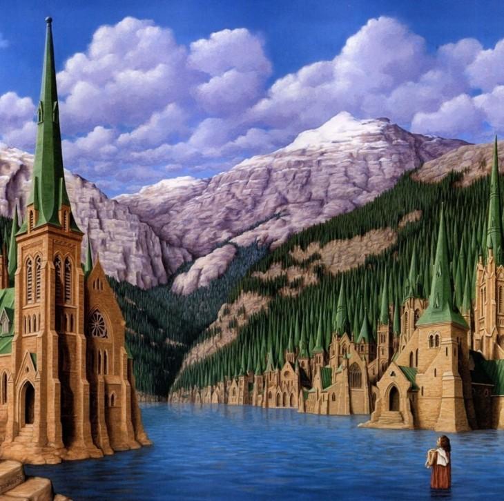 Un lago con algunos edificios con punta verde que a lo lejos se convierte en montañas con pasto verde