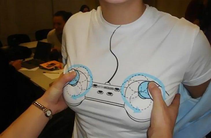 Playera con un control de videojuego y unas manos sobre el mismo