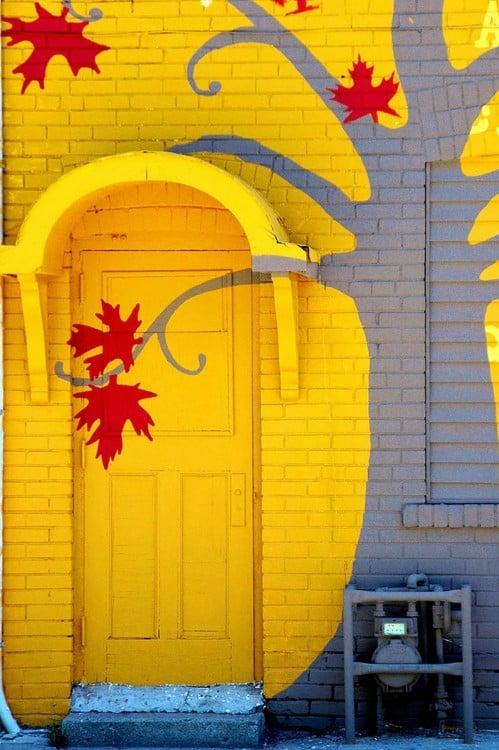 Puerta pintada en color amarillo que tiene un seguimiento de un árbol pintado en la pared con hojas parecidas a la bandera