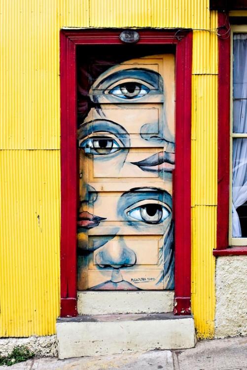 Puerta con un marco de color rojo y diferentes ojos pintados en la puerta