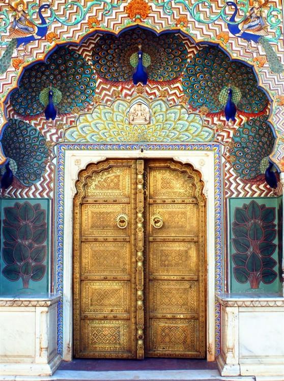 Puerta en un color dorado y en su contorno cuenta con pavo reales y sus colores predominantes son el azul