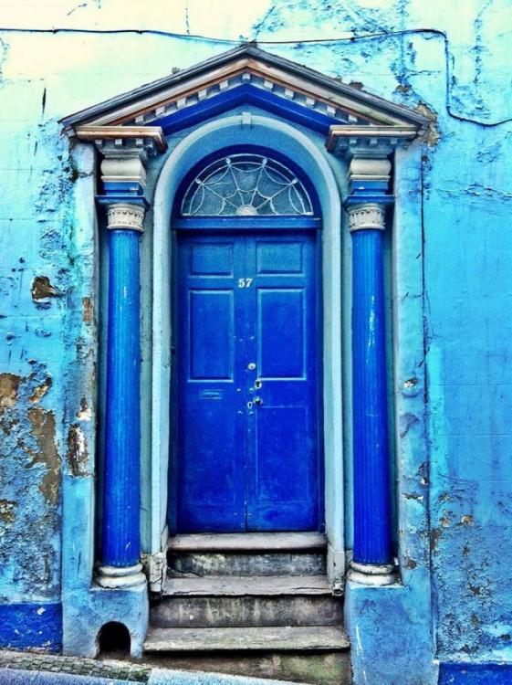 Puerta azul con barrotes en color azul con algunos escalones