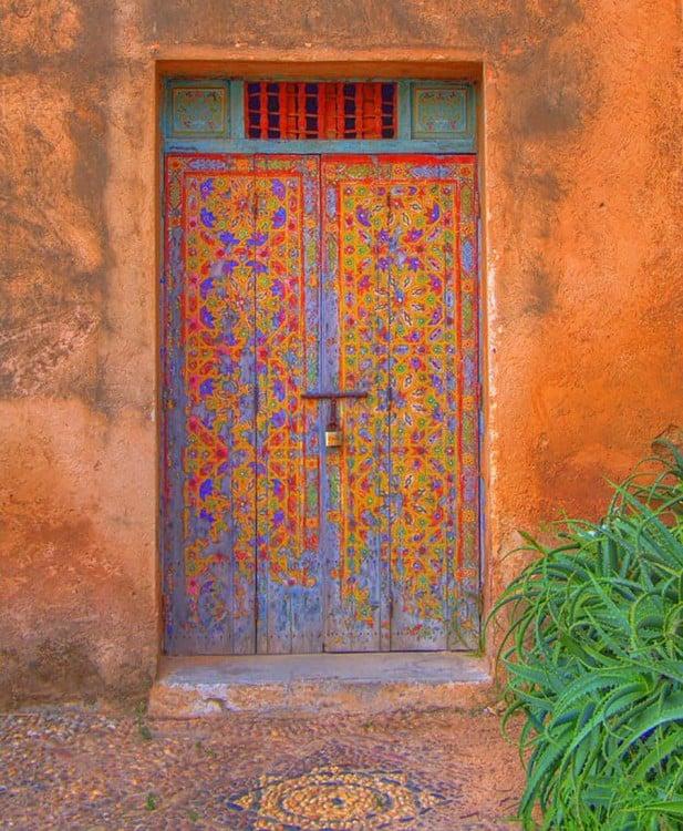 Puerta ubicada en Marruecos con una pequeña ventana en la parte superior y diseños en colores morados y anaranjados en su diseño