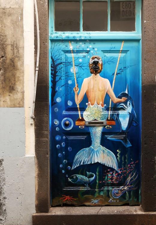 Puerta con un diseño de sirena en un columpio y un delfín frente de ella con algunos peces debajo simulando un mar