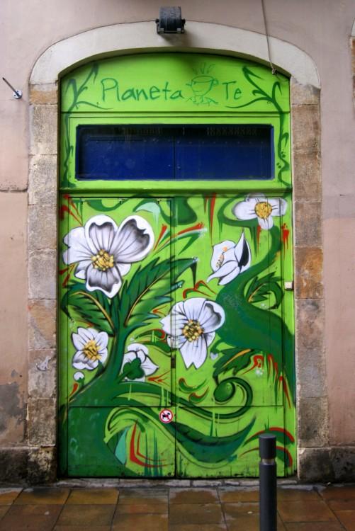 """Puerta en color verde con diseños de flores en la mayor parte de su superficie con un letrero en la parte superior que dice """"Planeta Té"""""""