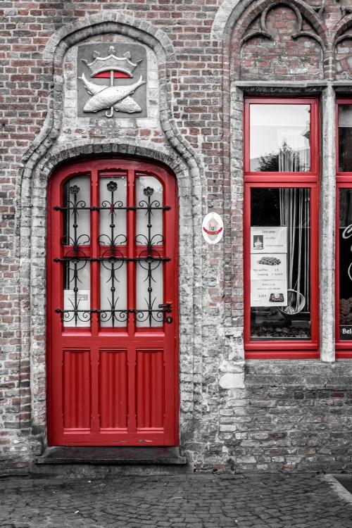 Puerta de color rojo con barandales en color negro que cubren tres filas de vidrios en la parte superior de la puerta