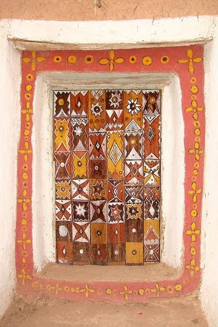 Puerta con un marco decorado con flores y cuadros con diferentes diseños