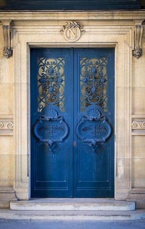 Puerta en color azul con barrotes y herrería con formas de flores