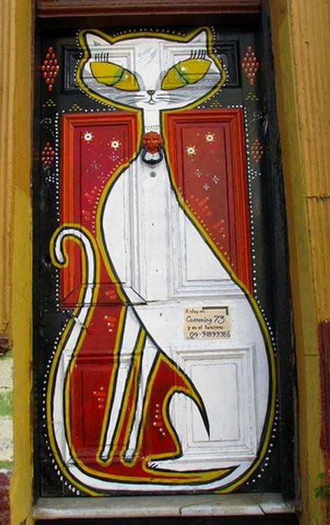 Puerta con el dibujo de un gato blanco con enormes ojos y el fondo color rojo