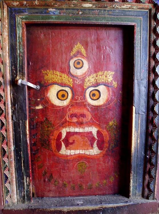 Puerta con el diseño de una cara con tres ojos en un fondo rojo