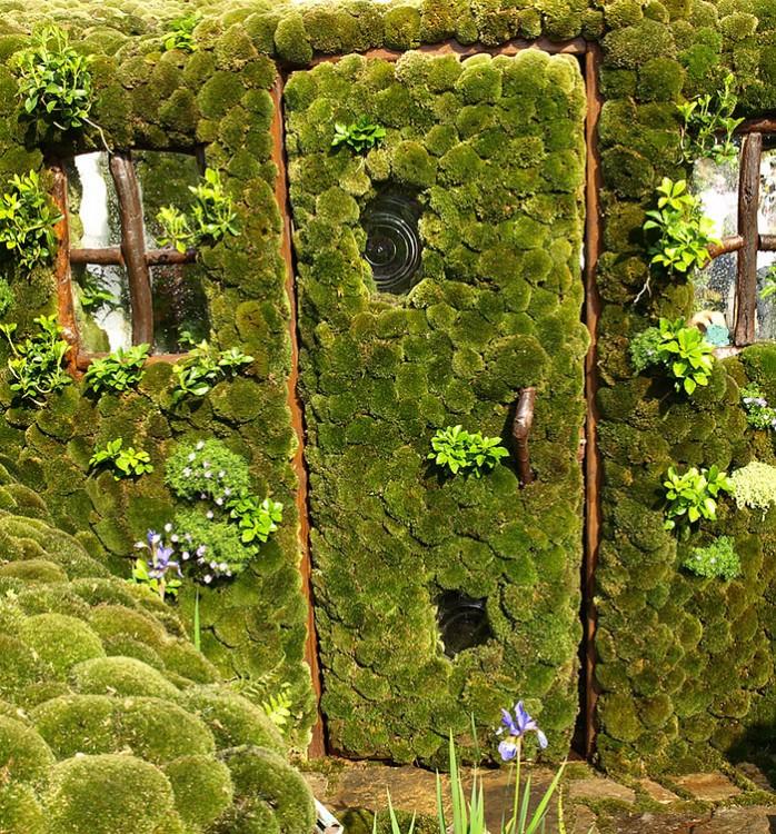 Casa que simula tener pasto tanto en sus paredes exteriores como en su puerta
