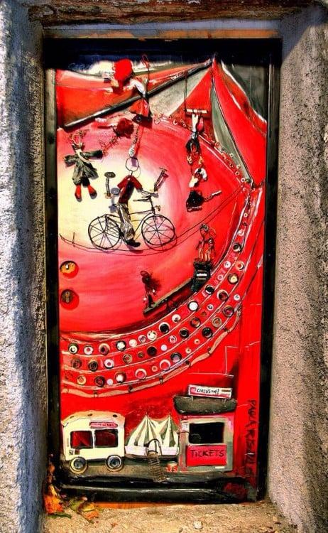 Puerta con un diseño de personas en bicicletas y simula tener un lugar donde salen tickets