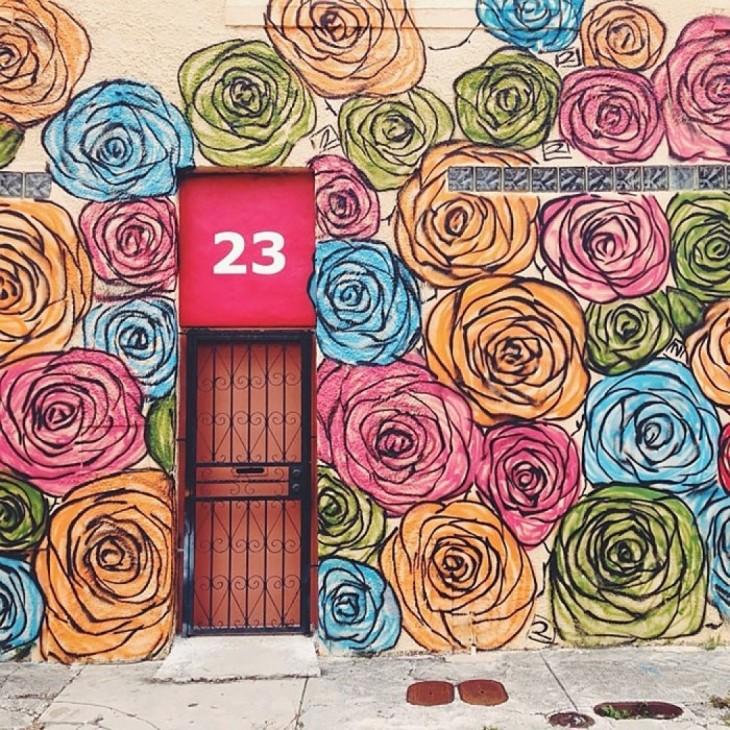 Casa con decoración de rosas alrededor de una puerta con barandal negro y un número 23 en un fondo rosa