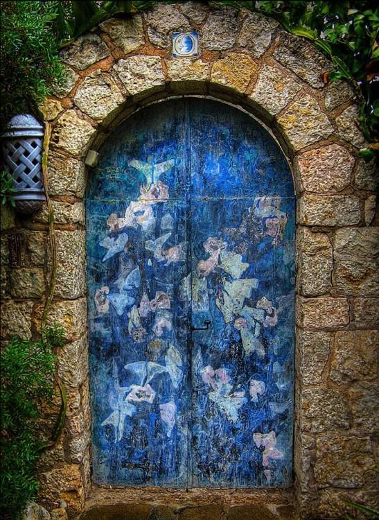Puerta que esta decorada en color azul y en su marco tiene contorneado por piedras