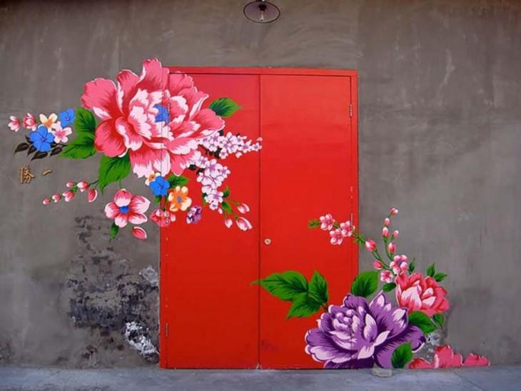 Puerta en color rojo con diseños de flores que van desde sus paredes en diferentes colores